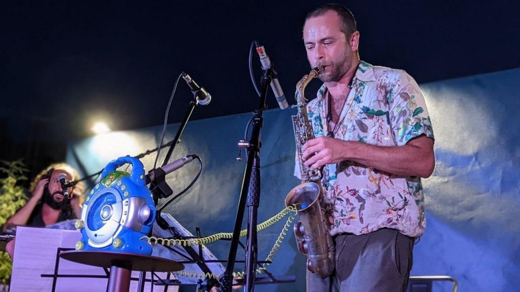 Folk e jazz dalle Città in Piena: Simone Alessandrini al sax (da cui spuntano i cavi du un karaoke giocattolo)